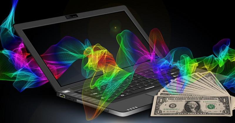 Computer, Geldscheine und bunter Strom