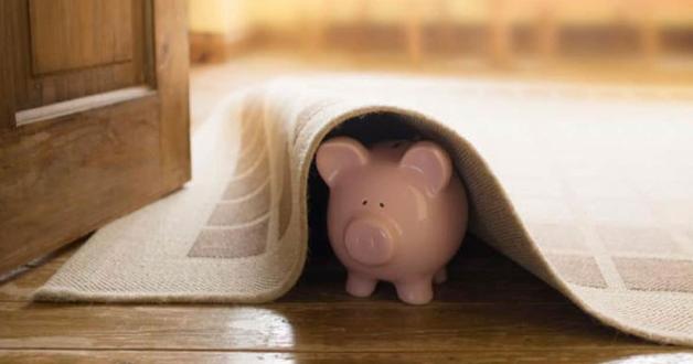ängstliches Sparschwein unter dem Teppich