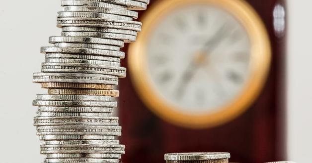 Münzen und ein Uhr im Hintergrund