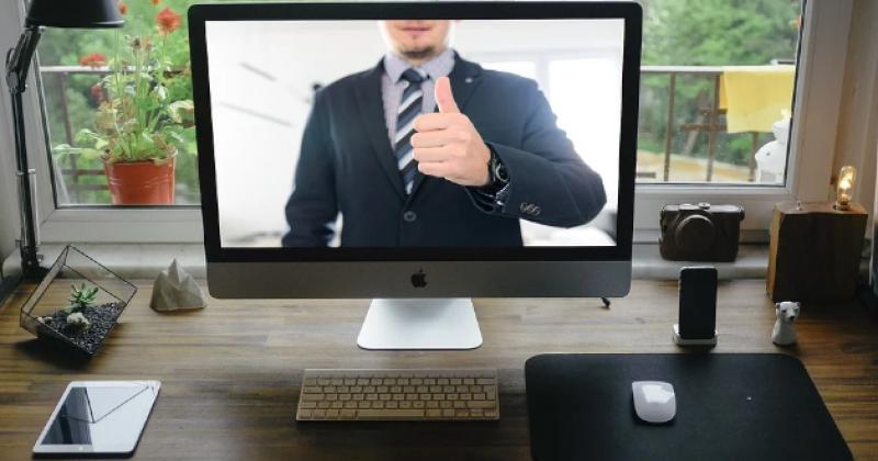 Ein Berater hebt seinen Daumen von einem Computerbildschirm in einem Raum
