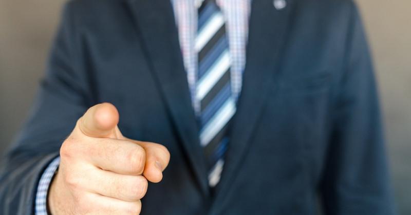 Ein Geschäftsmann zeigt mit dem Finger auf die Beobachter