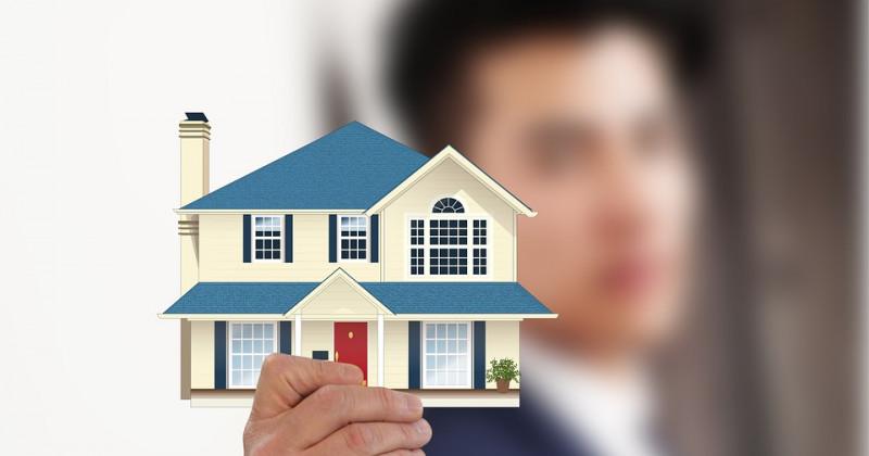 Ein Mann hält eine Silhouette eines Hauses hoch