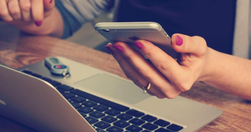Ein Mädchen fährt mit einer Computerzahlung fort, während sie ein Telefon in der Hand hält