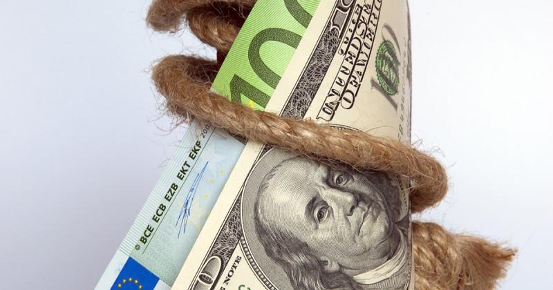 Ein Seil hält einen Dollarschein und einen Euroschein