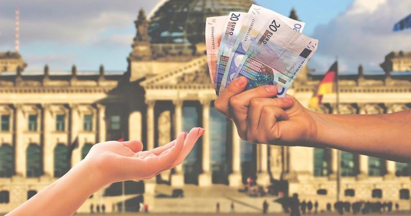 Eine Hand gibt einer anderen vor dem Deutschen Bundestag Geld