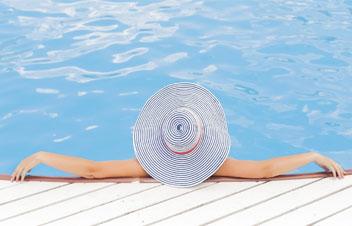 Mädchen mit dem Hut am Pool