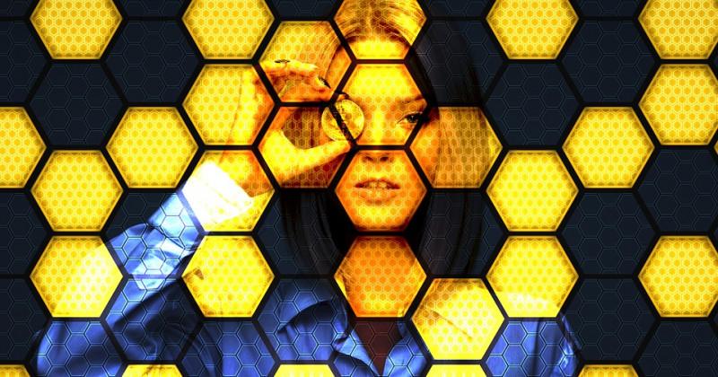 Frau schaut durch eine Münze aus einem Bildschirm