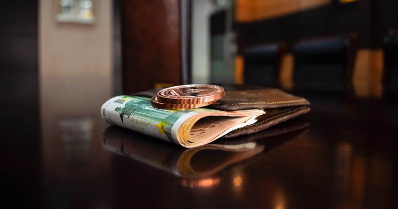 Geldscheine in einer Brieftasche mit einer darauf liegenden Münze