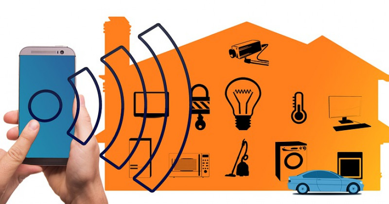 Hand klickt auf einen Telefonbildschirm, der mit Symbolen und dem Bild eines Hauses verbunden ist