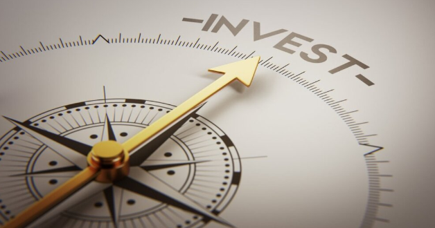 Kompass, der mit dem Pfeil auf das Wort investieren zeigt