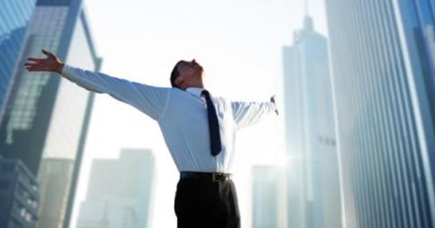 Geschäftsmann freut sich in einer sonnigen Stadt zwischen den Wolkenkratzern