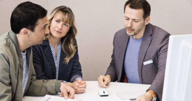 Ein Paar unterzeichnet einen Vertrag mit einem Berater