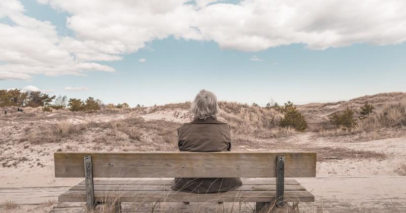 Ältere Frau sitzt auf einer Bank