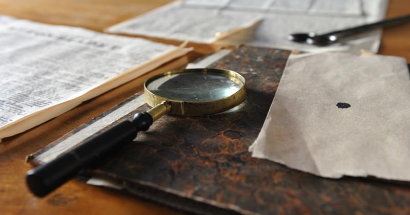 Lupe auf grünem Histogramm und anderen Dokumenten, die auf einem Tisch verstreut sind