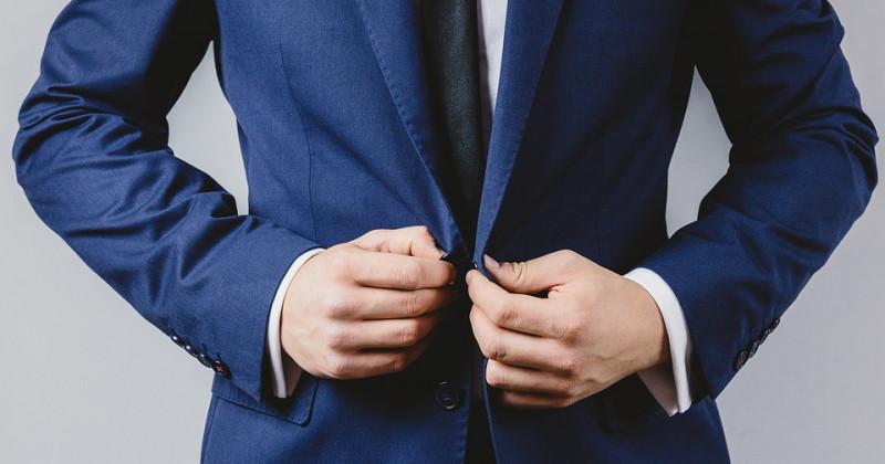 Mann im Anzug bindet seinen Anzug
