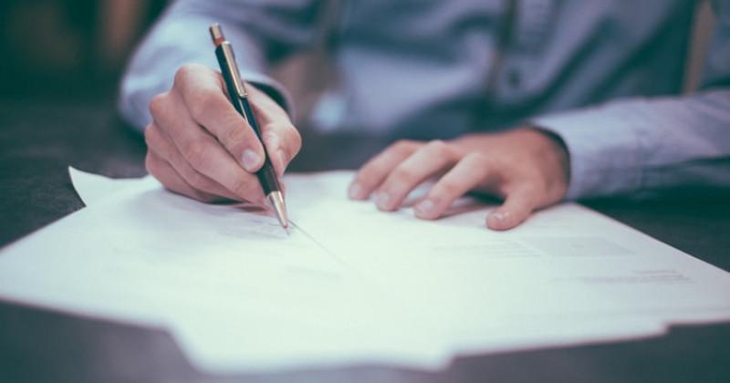 Mann schreibt auf ein Stück Papier
