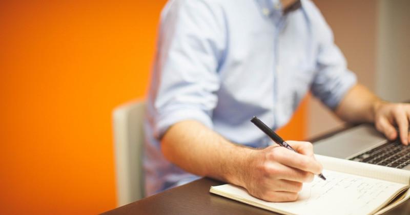 Mann schreibt in ein Heft, während er an seinem Computer arbeitet.