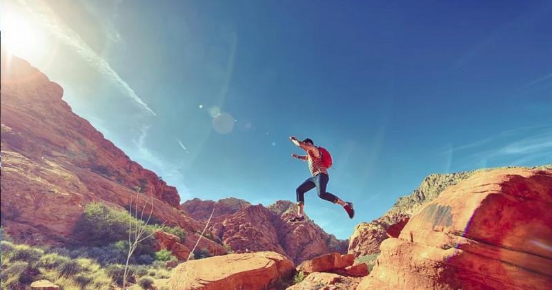 Mann springt zwischen felsigen Bergen