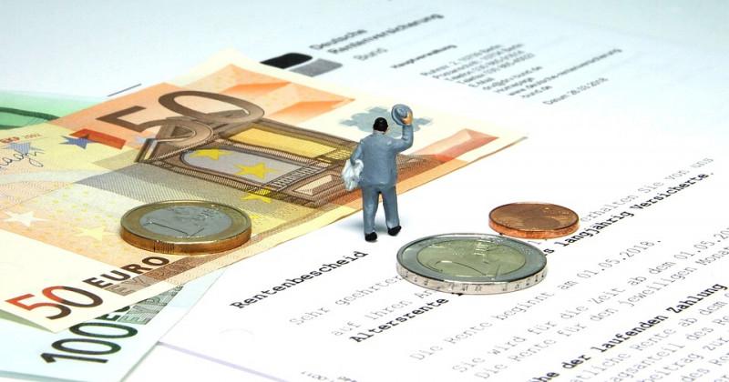 Miniaturfigur mit Münzen und Geldscheinen