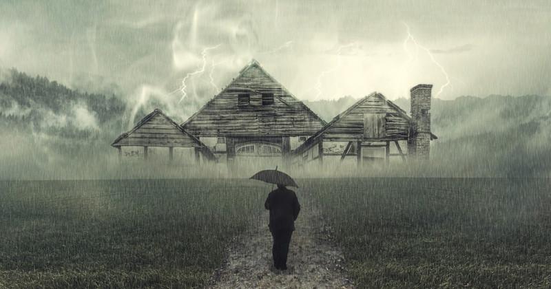 Regen, Mann mit Regenschirm vor einem verlassenen Haus