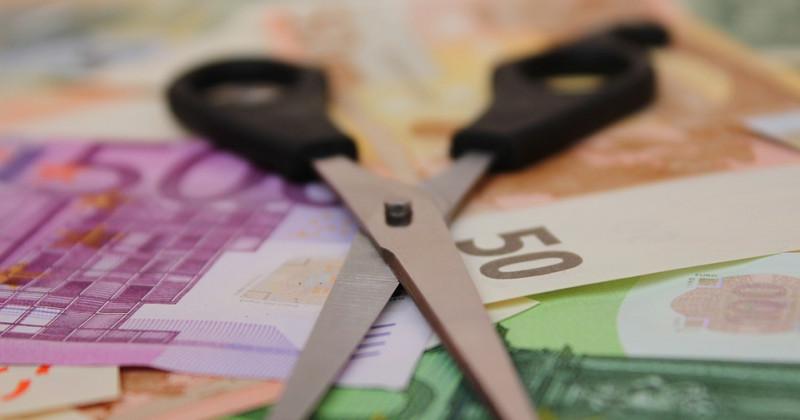 Schere ruht auf Geld