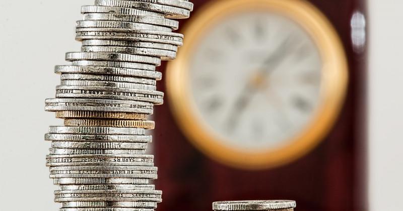 Stapel von Münzen, im Hintergrund eine unscharfe Uhr
