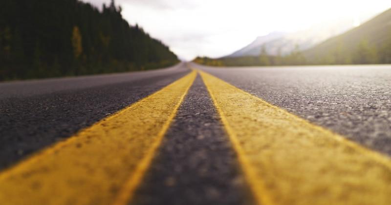Straße mit zwei gelben Linien in der Mitte, die geradeaus verläuft