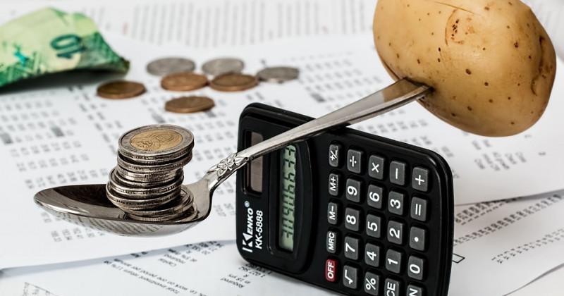 Taschenrechner, auf dem ein Löffel mit Münzen und einer im Griff steckenden Kartoffel ruht