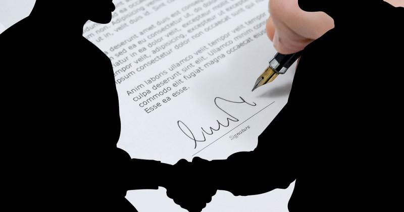 Vertragsunterzeichnung und Figuren von Menschen, die sich die Hände schütteln