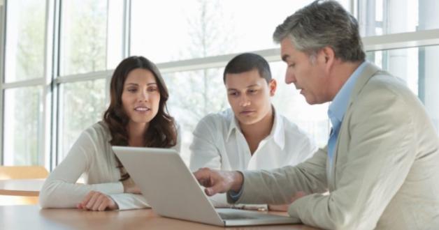 Paar während eines Termins mit einem Berater, der auf etwas auf einem Bildschirm zeigt