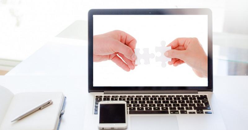 Zwei Hände verbinden zwei Puzzlestücke auf einem Bildschirm