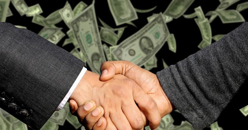 Zwei Menschen geben sich die Hand, während es hinter ihnen Geld regnet.