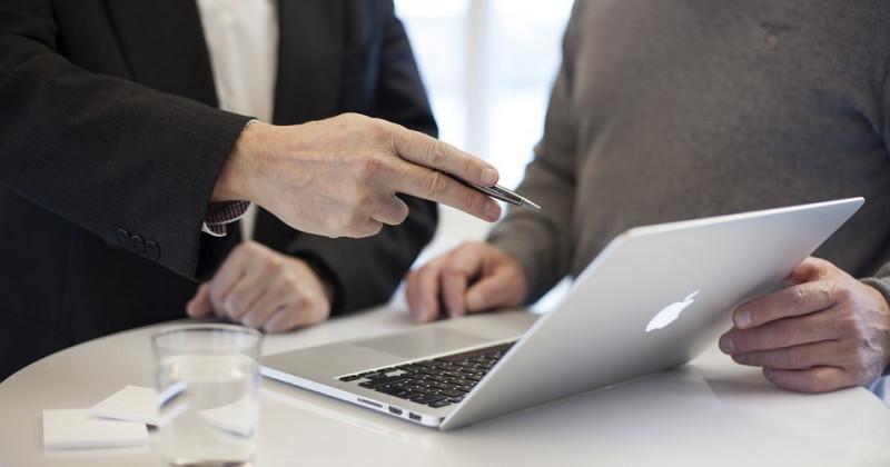 Zwei Personen zeigen auf einen Appel-Computer
